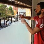 JECKERSON – Fase di applicazione del prespaziato del logo aziendale specchiato per vetrina.